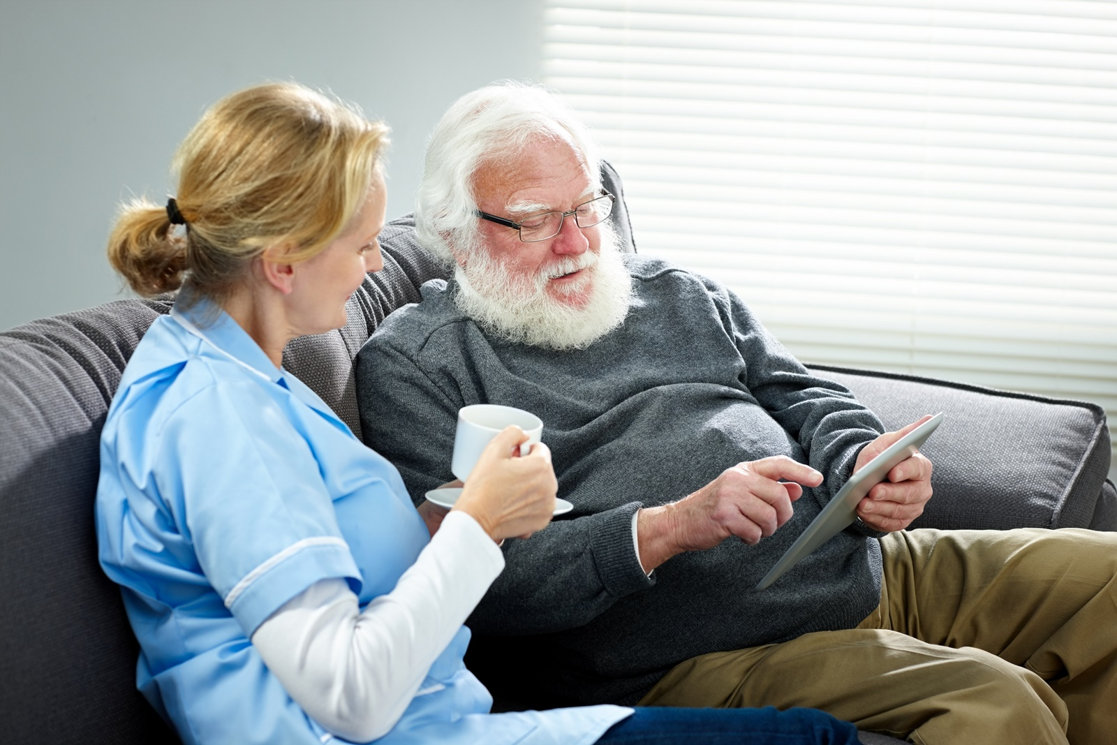 care worker with aged care resident and ipad